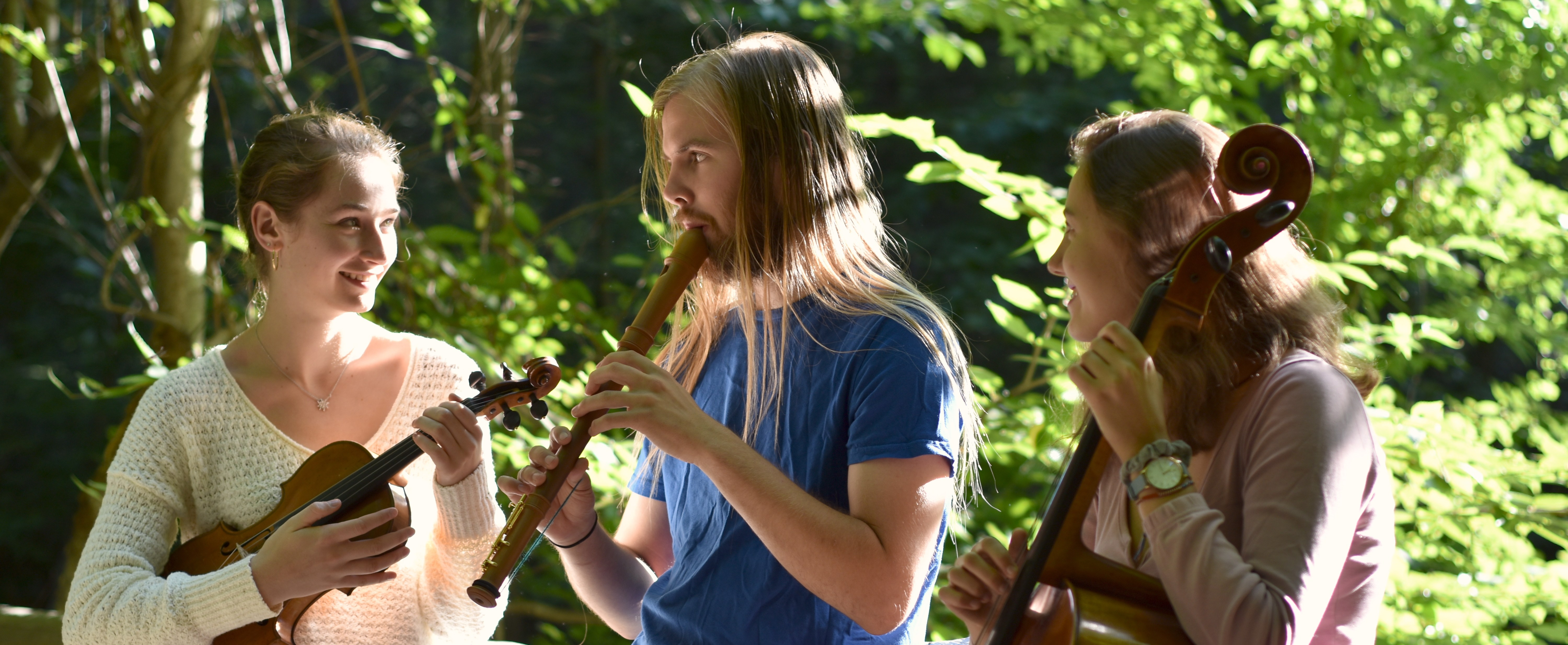 Lampyridæ (Lampyridae) homepage footer photo - The band playing their instruments casually in the woods.